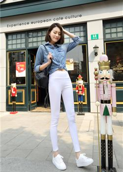 在欧式商店门口站着休息穿白色紧身裤和牛仔外套的美女